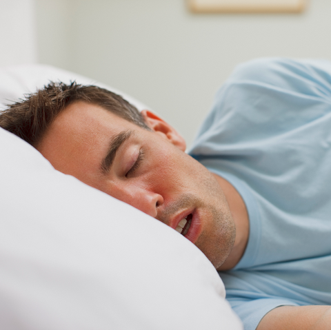 man laying bed with mouth open