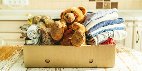 Donating concept - food, clothes, toys in cardboard