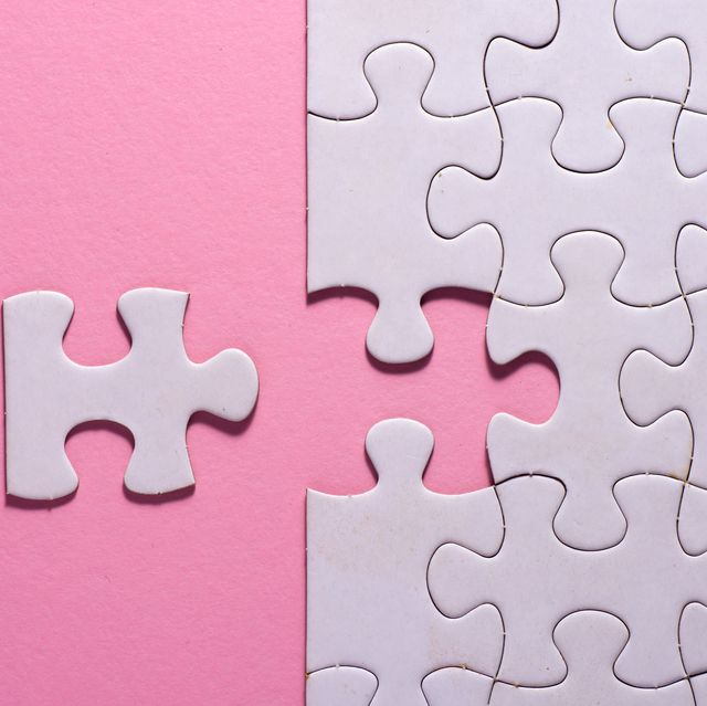 Incomplete white jigsaw puzzle pieces on pink background