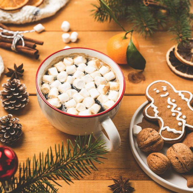 cup of hot chocolate with marshmallows and christmas decorations on wooden table closeup view cozy winter holidays composition