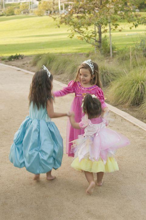 girls in princess dresses dancing together at park