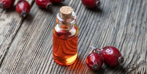 A bottle of rose hip seed oil with dried rose hips
