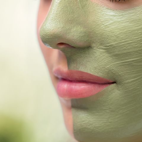 Extreme close up facial seaweed pealing on young woman.