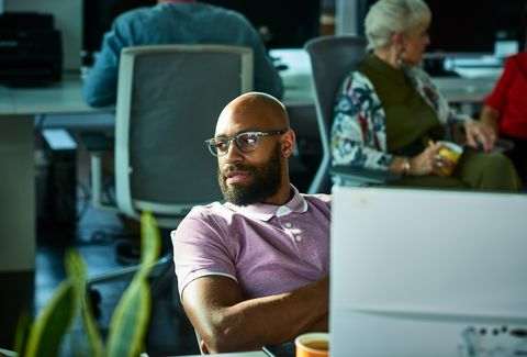 Candid portrait of African businessman wearing glasses looking away in office