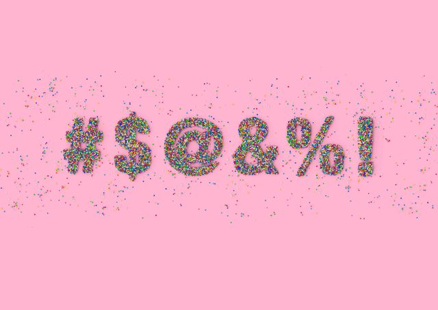 $ symbols made out of colorful candy sprinkles representing swearwords on pink background