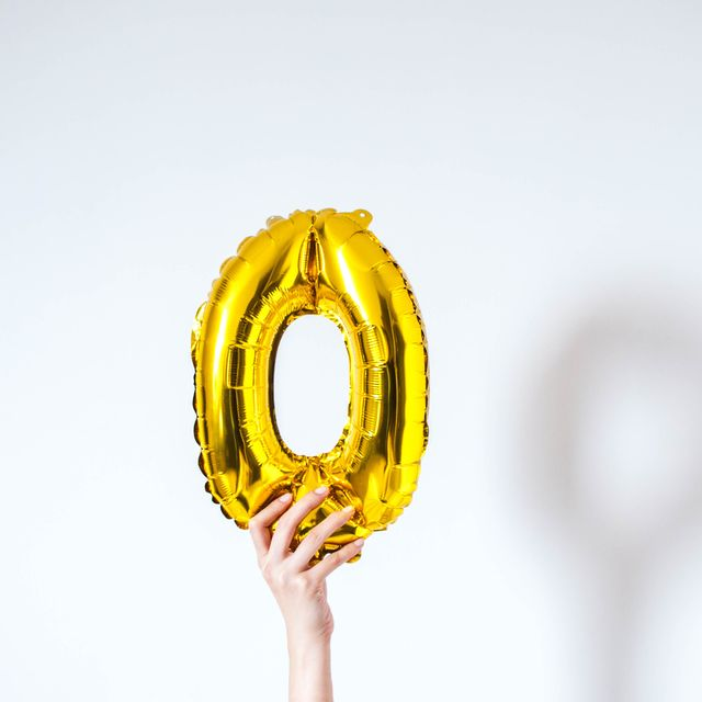 a young person is holding a golden colored number zero on a white background