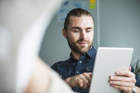 retrato de chico joven con camisa vaquera y coleta buscando información en tablet