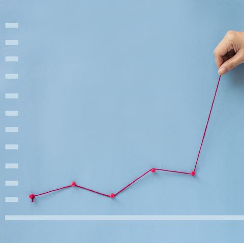 conceptual hand pulling business finance growth chart line upwards on blue background