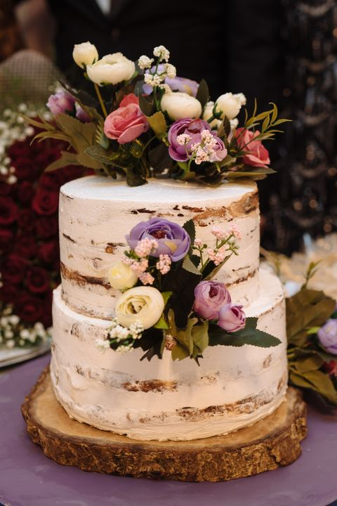 Cooking, sweetness, wedding concept. close up of two tier amazing cake with white and brown streeps and decorated with flowers