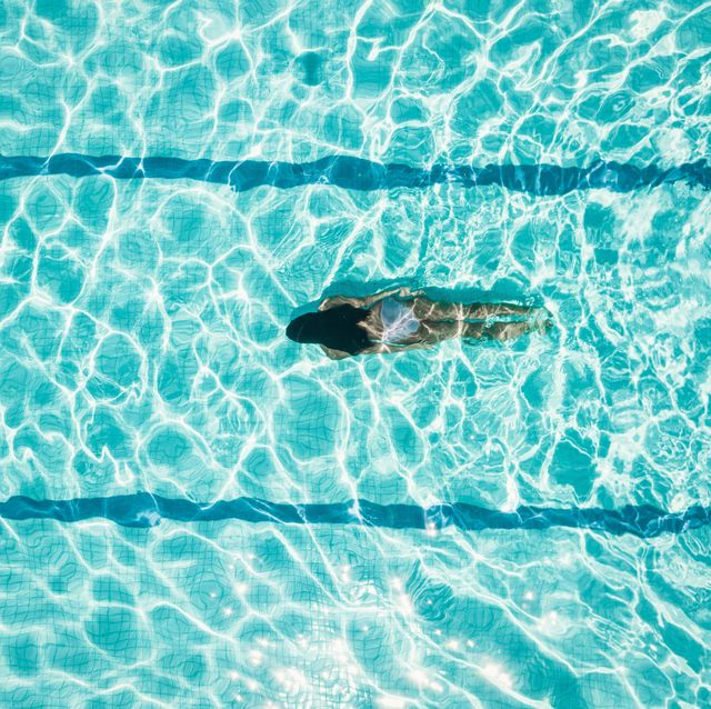 drone view on teenage girl diving in blue swimming pool