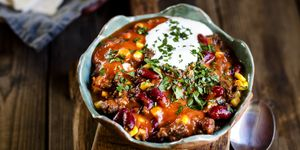 Chili con carne with kidney beans and corn, sour cream, parsley, tortilla bread