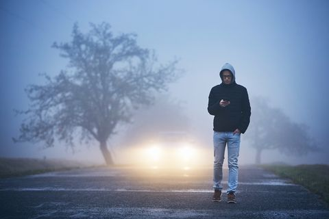 Man Using Phone While Walking On Road During Foggy Weather