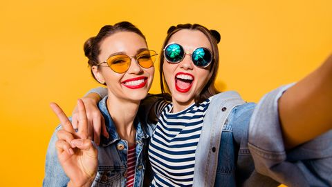 two glad positive grinning lady stand in glasses spectacles street style stylish trendy cool casual denim jeans clothes isolated on yellow background in take picture on cellular make hollywood smile