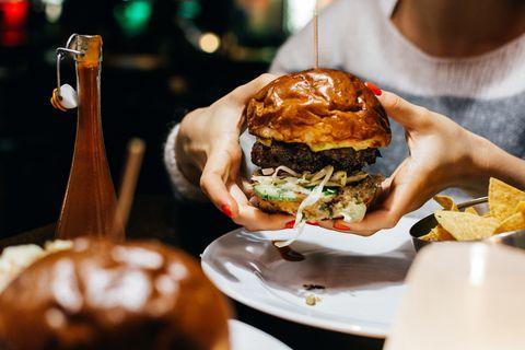 Close-Up Of Woman Holding Burger