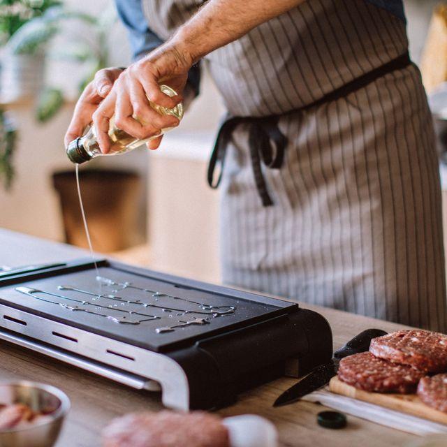 Male Cook Preparing Grill To Make Hamburgers
