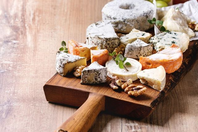 cheese plate assortment of french cheese served with honey, walnuts, bread and grapes on rustic wooden serving board over wood texture background close up photo by natasha breenredacouniversal images group via getty images