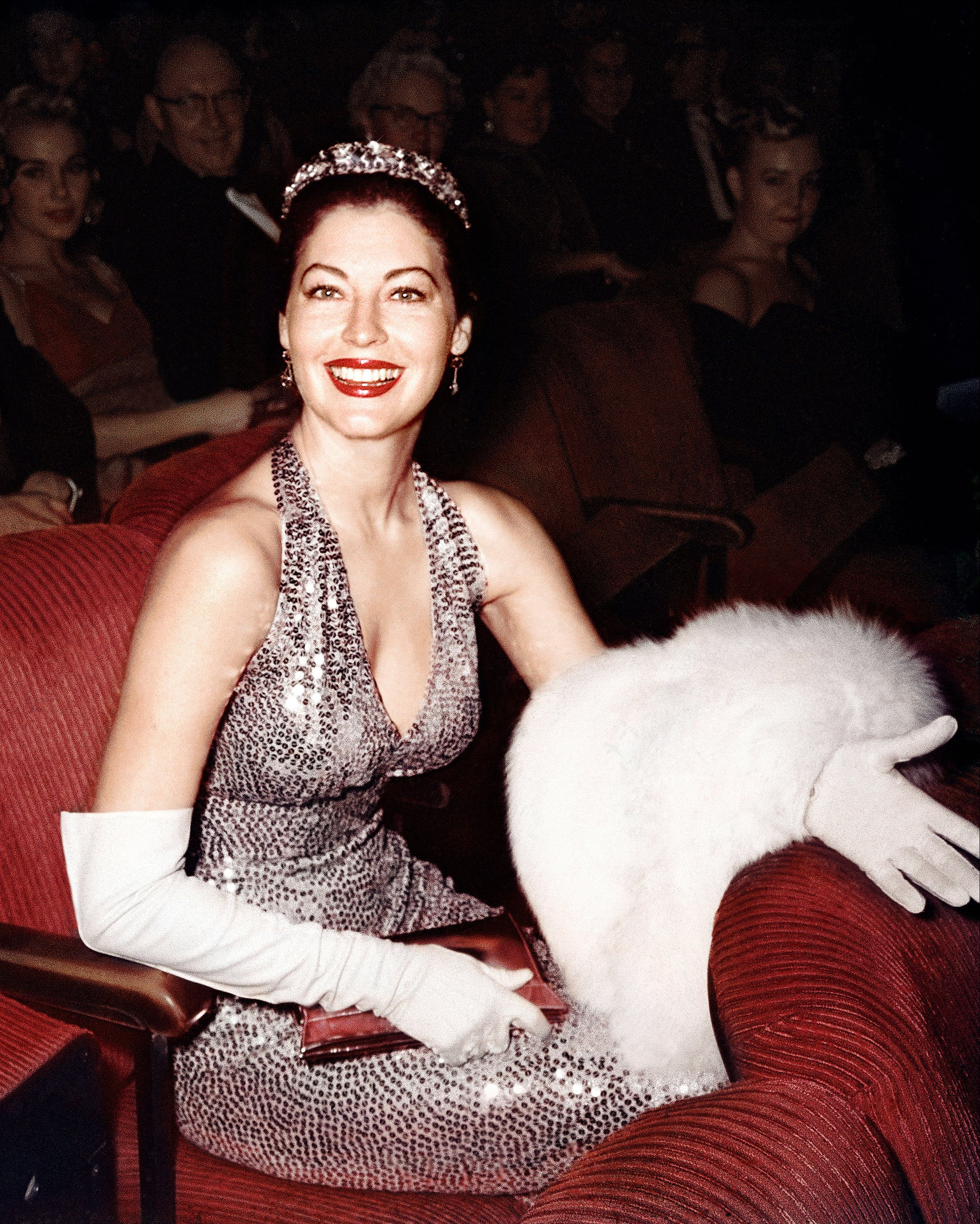 Ava Gardner looks like Hollywood royalty in a bejeweled gown, elegant gloves, and tiara.