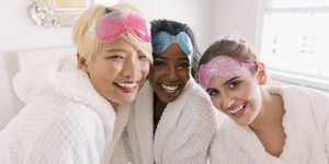 Portrait happy young women friends in bathrobes and eye masks