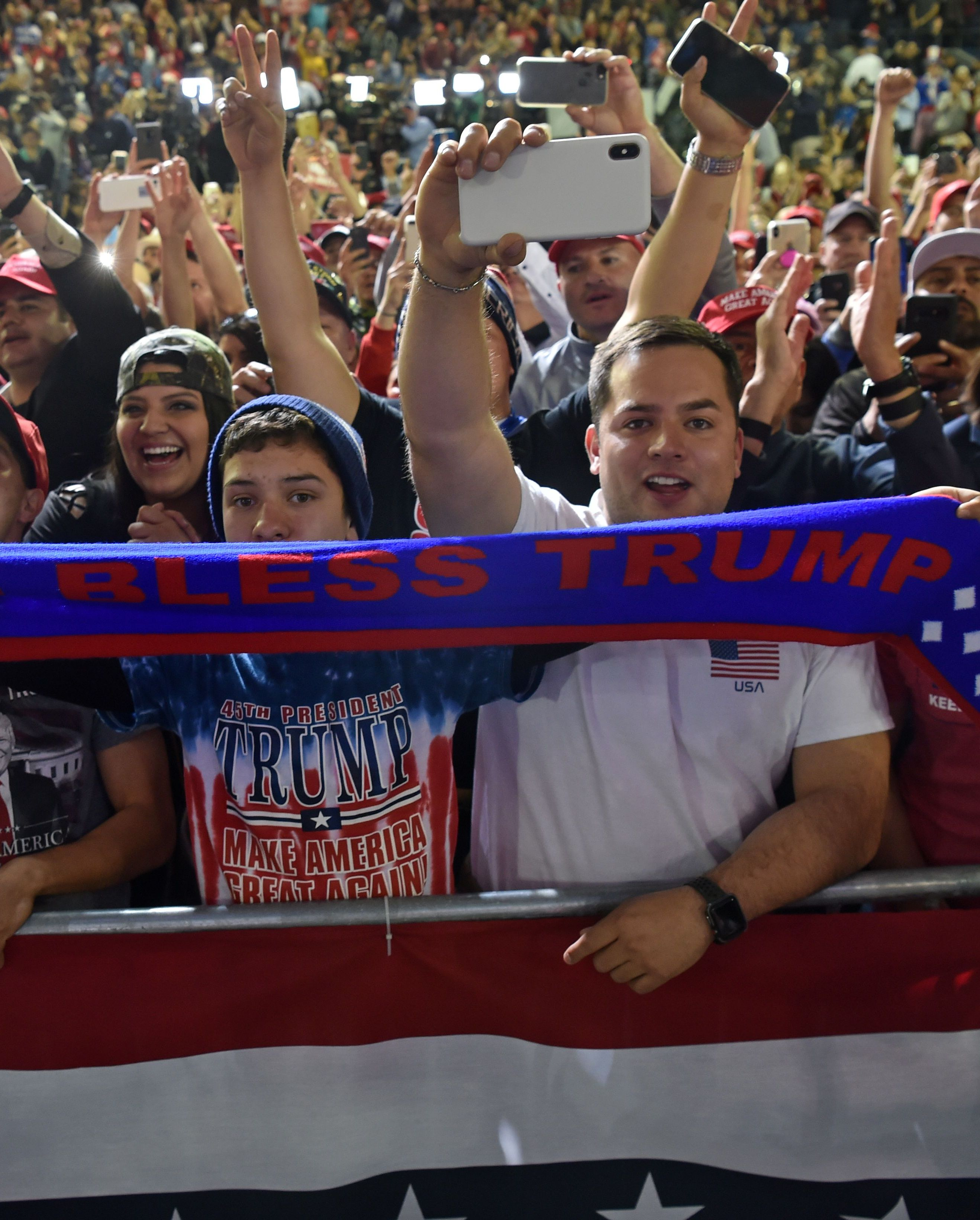 """Supporters of Donald Trump hold a sign that says, """"God Bless Trump,"""" during a rally in El Paso."""