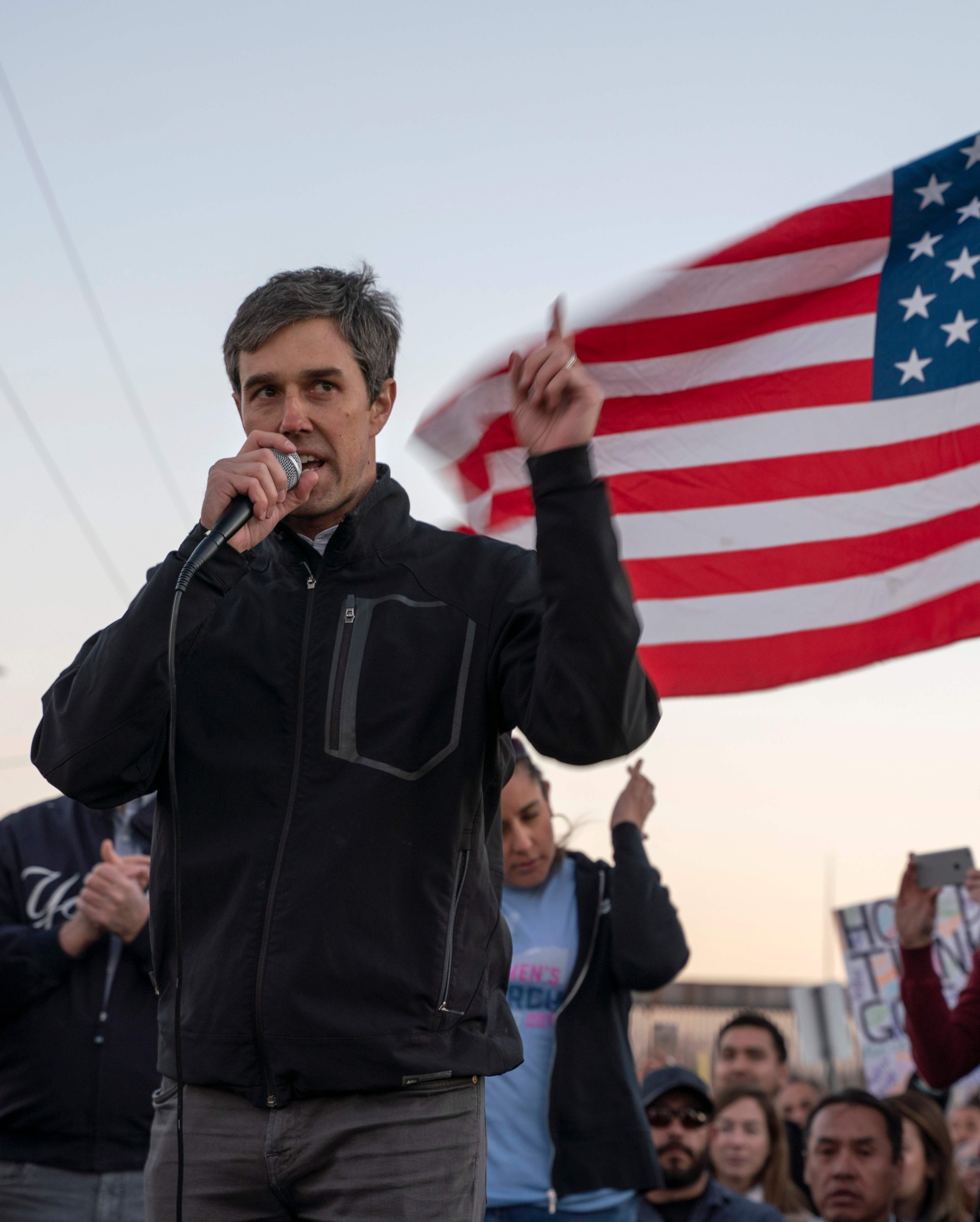 """Beto O'Rourke speaks to a crowd of marchers during the """"March for Truth"""" in El Paso on Monday. The march took place at the same time as Trump's rally and culminated at a rally inside a baseball stadium."""