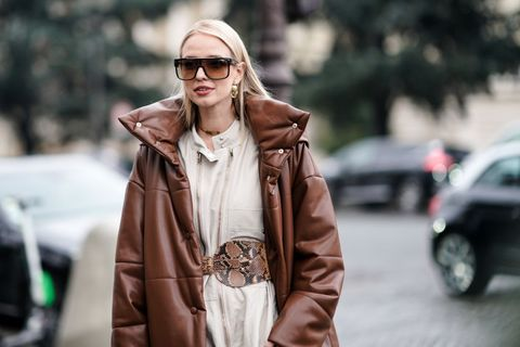 paris, france   january 22 leonie hanne wears a brown long puffer coat, a vuitton bag, a white jumpsuit, a snake print large belt, snake print boots, outside alexandre vauthier, during paris fashion week   haute couture spring summer 2020, on january 22, 2019 in paris, france photo by edward berthelotgetty images
