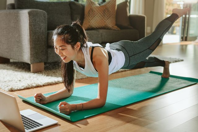 smiling woman exercising at home and watching training videos on laptop chinese female doing planks with a leg outstretched and looking at laptop
