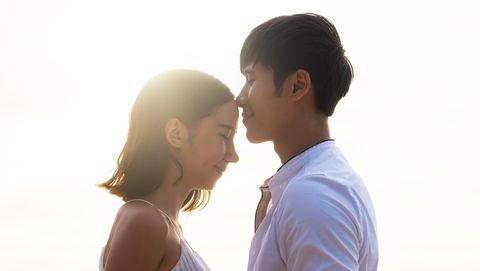 young asian couple or lover kiss on the beach with evening light young lovers on vacation
