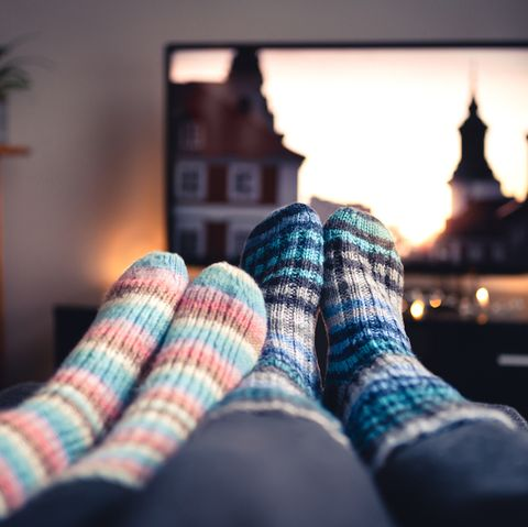 Couple with socks and woolen stockings watching movies or series on tv in winter. Woman and man sitting or lying together on sofa couch in home living room using online streaming service.