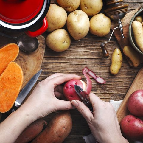 Woman hand peeling a potato, top view.  Variety of raw uncooked organic potatoes: red, white, sweet and finger potatoes over wooden background.