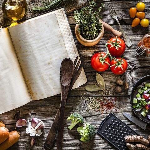 Cookbook with vegetables, spices and herbs shot from above on rustic wooden table