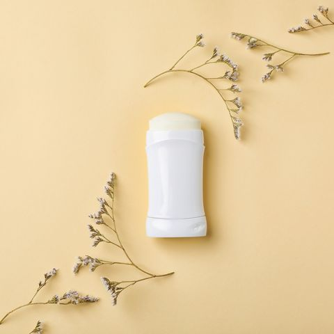 White deodorant and herbs on color background