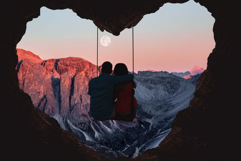 composition of the alps mountains during sunset with full moon and couple on swing from a heart shape cave