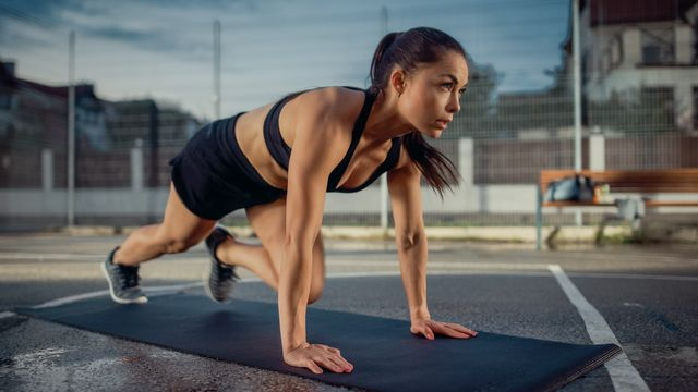 beautiful energetic fitness girl doing mountain climber exercises she is doing a workout in a fenced outdoor basketball court evening after rain in a residential neighborhood area