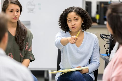 a serious female high school student sits in a circle with a group of classmates and takes a questions as she leads a study group discussion  she uses her pencil to point to an unrecognizable classmate
