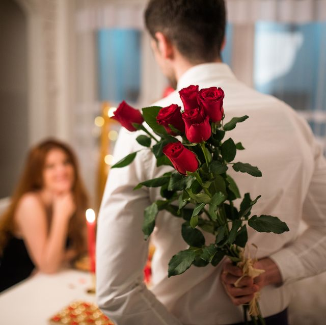happy woman looking at her boyfriend holding bouquet of roses behind his back