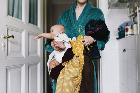 Single Mother With Baby Trying To Get Dressed
