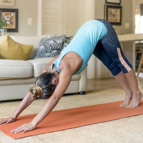 sporty woman practicing yoga in living room at home