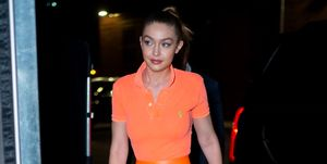 Gigi Hadid in long orange slip skirt and orange polo shirt