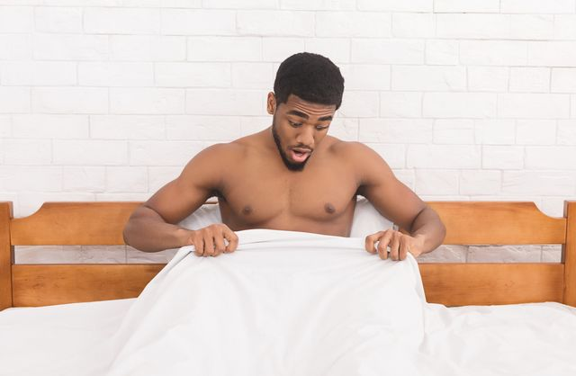 trouble with erection young african american man in bed having problems with potency, looking at his penis under blanket, copy space