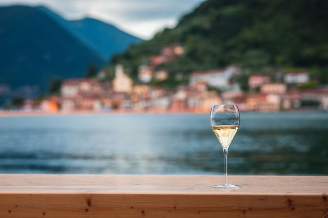 glass of franciacorta wine with the view of monte isola, during the installation entitled the floating piers created by artist christo vladimirov javacheff on iseo lake