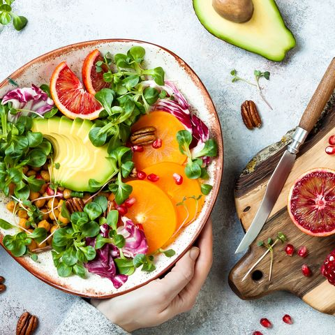 vitamin c foods girl holding vegan, detox buddha bowl with turmeric roasted  chickpeas, greens, avocado, persimmon, blood orange, nuts and pomegranate