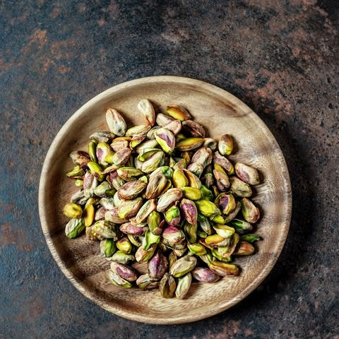 a heap of pistachios on a plate on rusty background