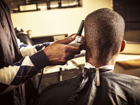 man getting buzz cut at barber shop