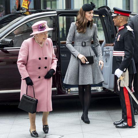 Street fashion, Fashion, Coat, Standing, Trench coat, Uniform, Overcoat, Street, Pedestrian, Outerwear,