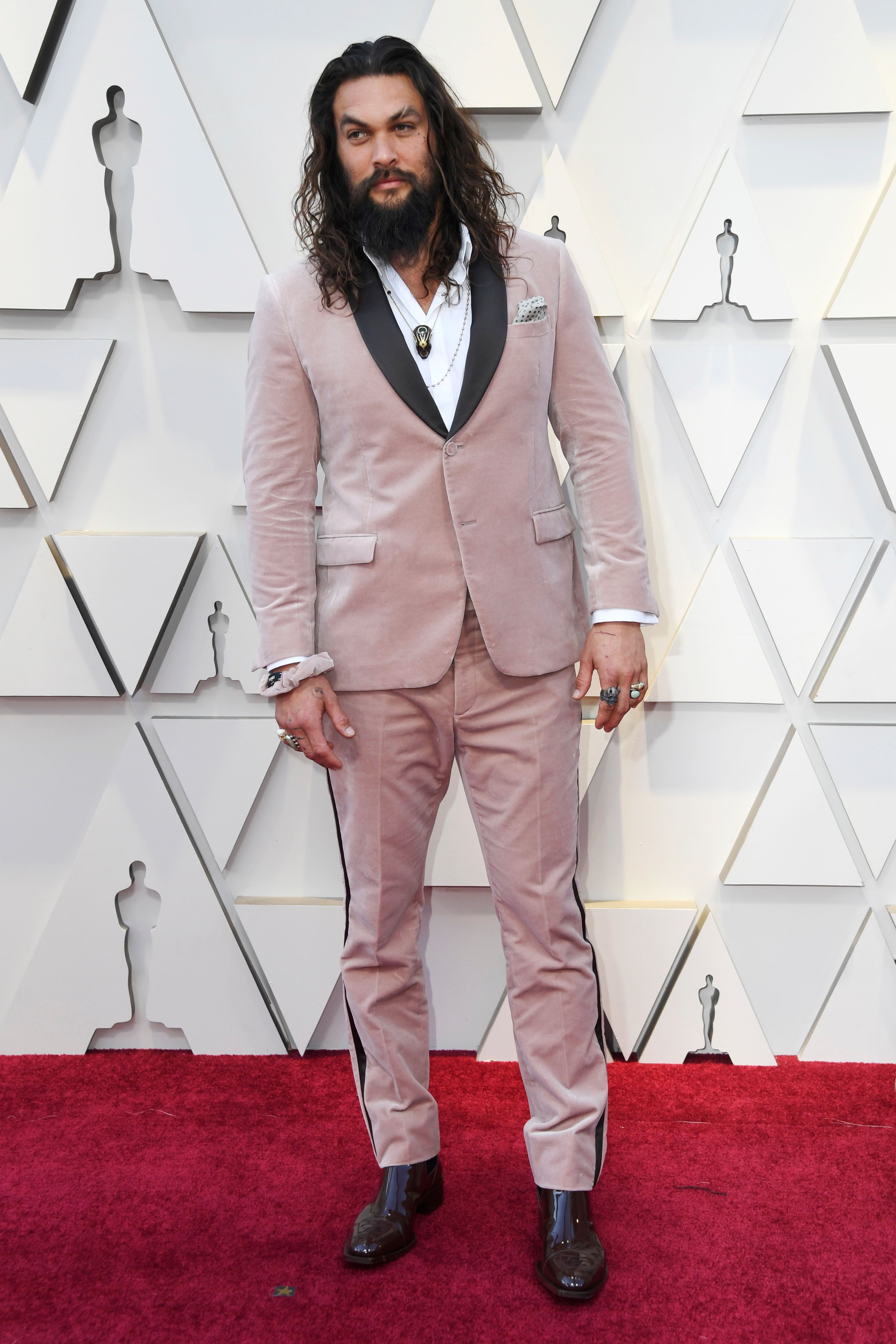 Jason Momoa at the Oscars in a pink Fendi tux with matching scrunchie.