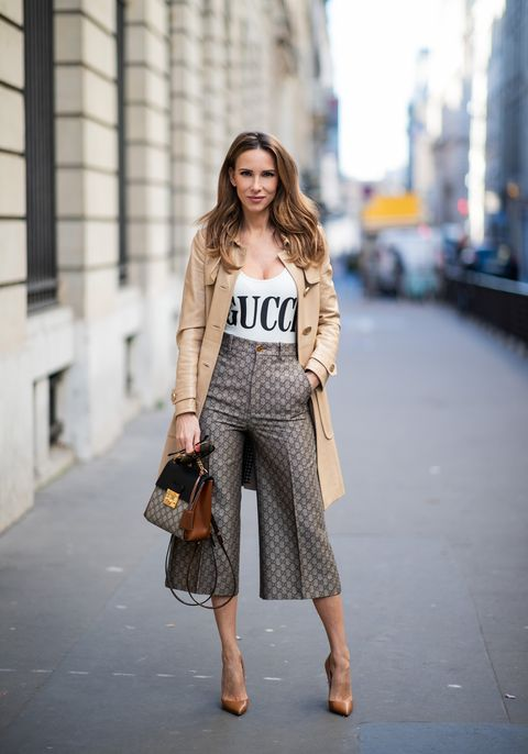 paris, france   february 25 alexandra lapp is seen wearing a gucci culotte with the monogram pattern, brown and black gucci backpack with monogram pattern, a sparkling white swimsuit with the gucci logo print, vintage leather trenchcoat from gucci, so kate christian louboutin heels in cognac during paris fashion week womenswear fallwinter 20192020 on february 25, 2019 in paris, france photo by christian vieriggetty images