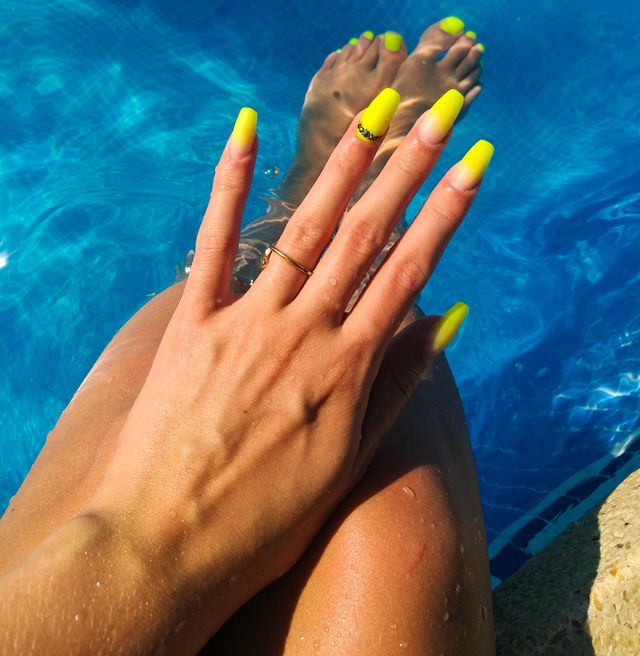 close up of fake nails, acrylic nails, gel nails on a womans hand in neon colours in a swimming pool