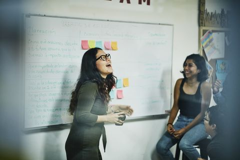 Laughing female engineer leading project discussion with coworkers in workshop