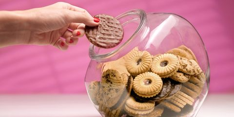 dieting woman sneaking a biscuit treat from the cookie jar