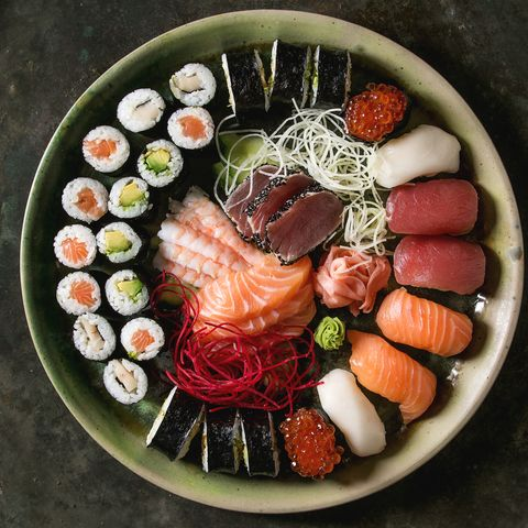 sushi set nigiri sashimi and sushi rolls in ceramic serving plate with salad over dark metal texture background flat lay, space japan menu